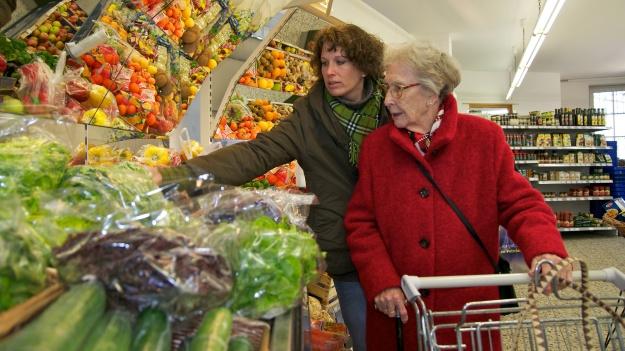 Ältere Dame beim einkaufen mit Betreuerin